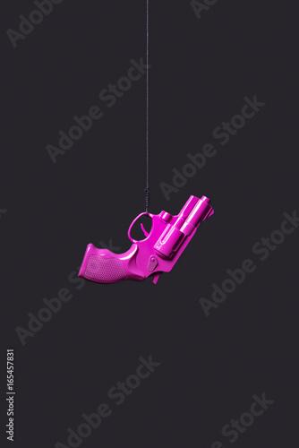 Fotografía  pistola ahorcada rosa sobre fondo negro