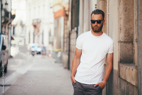 Foto  Hipster handsome male model with beard wearing white blank t-shirt with space fo