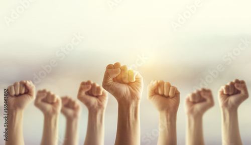 Vászonkép  Peoples raised fist air fighting and sunlight effect, Competition, teamwork concept, background space for text