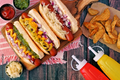 Hot dogs with assorted toppings and potato wedges, overhead scene on a rustic wood background