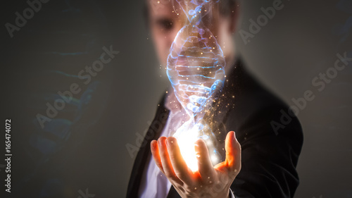 Photo close up of Businessman holding glowing DNA helix with energy sparks