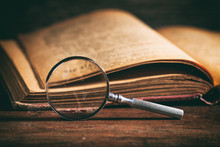 Vintage Book And Magnifying Glass On Wooden Desk