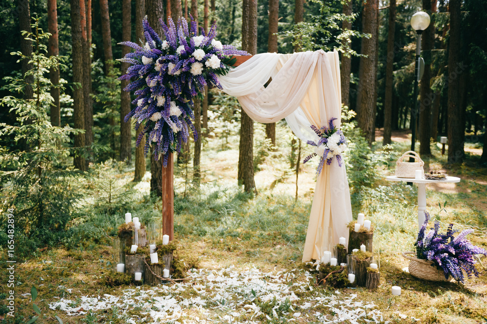 Fototapety, obrazy: Wedding wooden arch for marriage ceremony with flowers, curtain and other decoration elements standing on ground in forest. Pine trees in sunny summer day. Celebration mood. Candles in glass, feathers