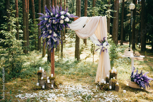 Wedding wooden arch for marriage ceremony with flowers, curtain and other decoration elements standing on ground in forest Fototapete
