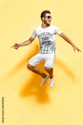 Shot of handsome bearded guy dressed in white t-shirt and shorts jumping looking at camera smiling.
