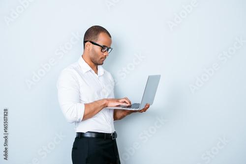 Fotografija  Confident pensive young mulatto americano market broker is looking at his laptop