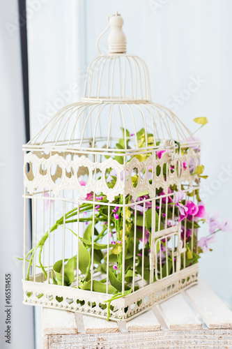 Fotografia  Shabby chic decorating with beautiful vintage birdcage and flowers