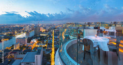 Fotografie, Obraz  Dining table with beautiful city view on rooftop at twilight scene