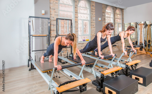 Photo  Young women exercising on pilates reformers beds