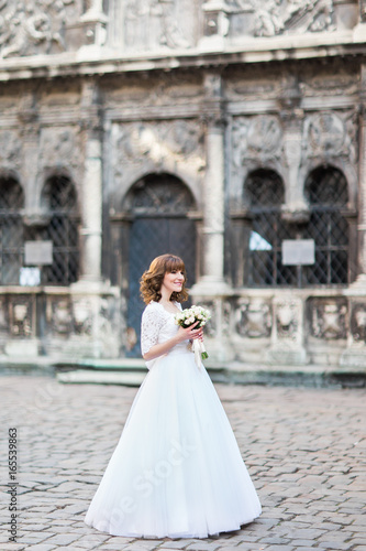 Fényképezés Full-length side view of the smiling bride holding the wedding bouquet in the street