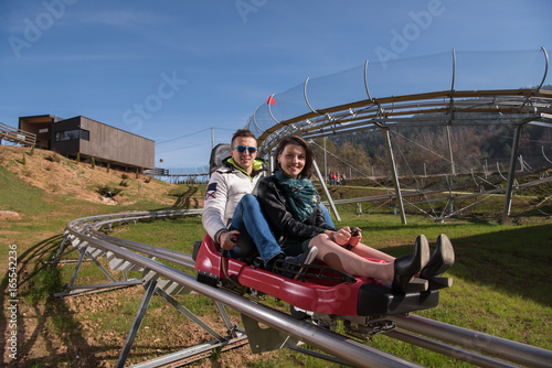 Photo  couple enjoys driving on alpine coaster