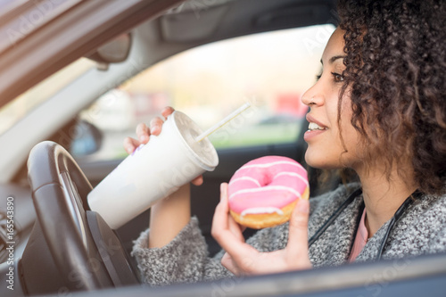 Fototapeta Woman eating a sweet and drinking driving a car obraz
