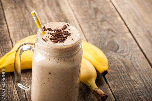 Banana chocolate smoothie and banana on wooden table