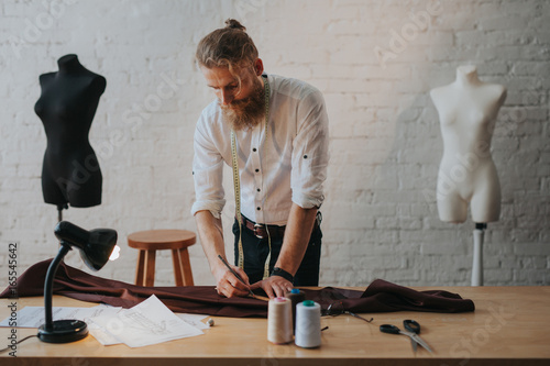 Man creating new clothes in parlour Canvas Print