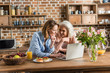 two women, senior and young using laptop at table in kitchen