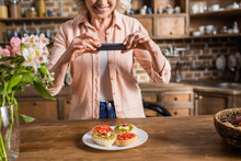 Portrait Of Senior Woman Photographing Plate With Food At Kitchen