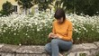 A young brunette woman in a yellow turtleneck uses a white smartphone and sighs sitting next to blooming daisies on a summer or spring afternoon.