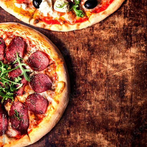 Fresh baked Hot pizza slice with cheese on a rustic wooden table  closeup. © nataliazakharova