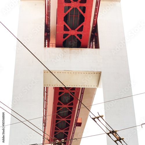 Fototapeta  The 25 de Abril bridge over city buildings or residential quarter in Lisbon, Portugal