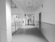 Lungo corridoio di ospedale con donna sullo sfondo in bianco e nero