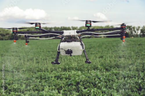 Agriculture drone spraying water or pesticides to grow over green field. Smart farming concept.