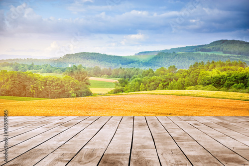 Poster Melon landscape of golden wheat field in summer season with wood top surface