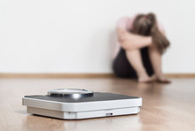 Weight Loss Fail Concept. Scale And Depressed, Frustrated And Sad Woman Sitting On Floor Holding Head And Arms On Knees.