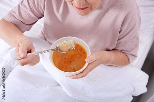 Elderly woman sitting in bed and eating soup, closeup