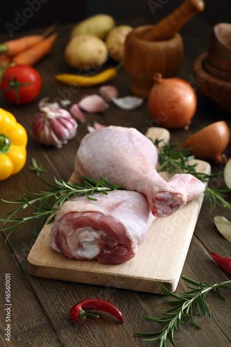 Staande foto Vlees carne cruda coscia di pollo otacchino sfondo tavolo di cucina rustico