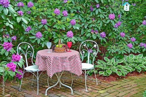 Plakat kosz owoców na stole z krzesłami na patio z cegły w ogrodzie rododendronów