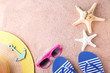 Flip flops with starfish, sunglasses and hat on the beach sand