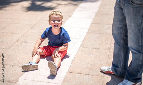 Crying capricious boy is sitting on the road Tablou Canvas