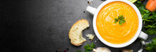 Carrot Cream-soup On Black Table. Long Banner Format.