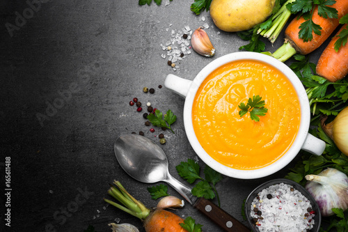 Foto op Canvas Klaar gerecht Carrot cream-soup on black table.