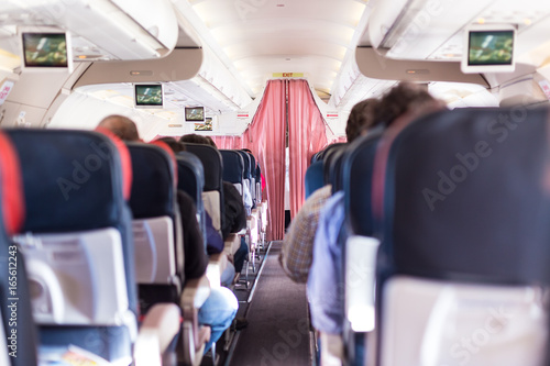 Tuinposter Interior of commercial airplane with passengers on seats during flight. The curtain separates economy from business class.