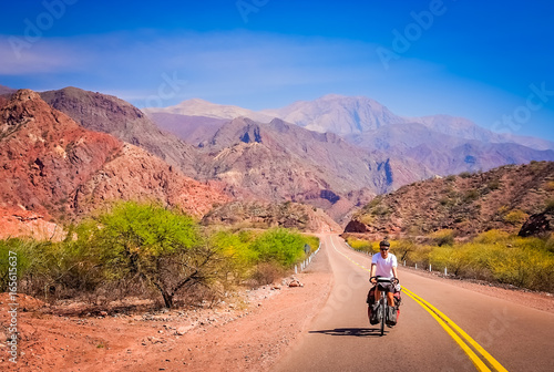 In de dag Route 66 Man cycling on the empty road to Cafayate