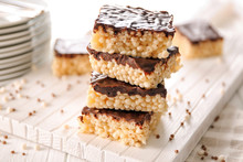 Delicious Rice Crispy Treats With Chocolate On Wooden Board