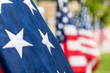 Horizontal photo of a close up of the white stars on a blue background of the American flag and several other US flags in soft focus in the background