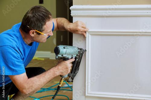 Cuadros en Lienzo Carpenter using a brad nail gun to complete framing trim
