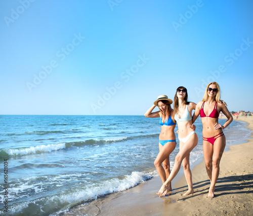 Plakat Grupa szczęśliwi przyjaciele ma zabawę przy ocean plażą