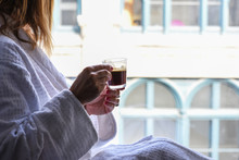 Woman Sitting In Window In White Robe Holding Cup Of Cappuccino
