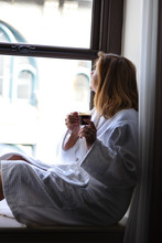 Woman Sitting In Window Holding Cup Of Cappuccino Looking Outside In Morning