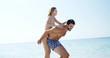 Man giving piggyback ride to woman at beach