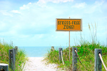 STRESS-FREE ZONE Sign At Beutiful Beach With Sandy Path Down To The Calm Blue Ocean Water With Soft White Clouds In The Sky.