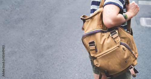 Close up backpack at back of woman traveler walking on street to sightseeing town,Travel concept,leave copy space for adding text