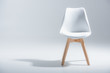 canvas print picture - Studio shot of stylish chair with white top and light wooden legs standing on white