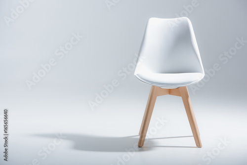 Fotografie, Obraz Studio shot of stylish chair with white top and light wooden legs standing on wh
