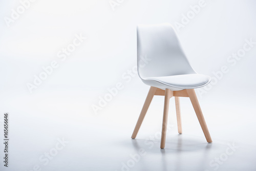 Studio shot of stylish chair with white top and light wooden legs standing on wh Fototapeta