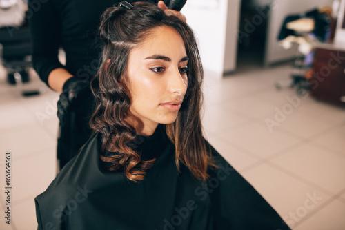 Spoed Foto op Canvas Kapsalon Stylist curling woman's hair in beauty salon