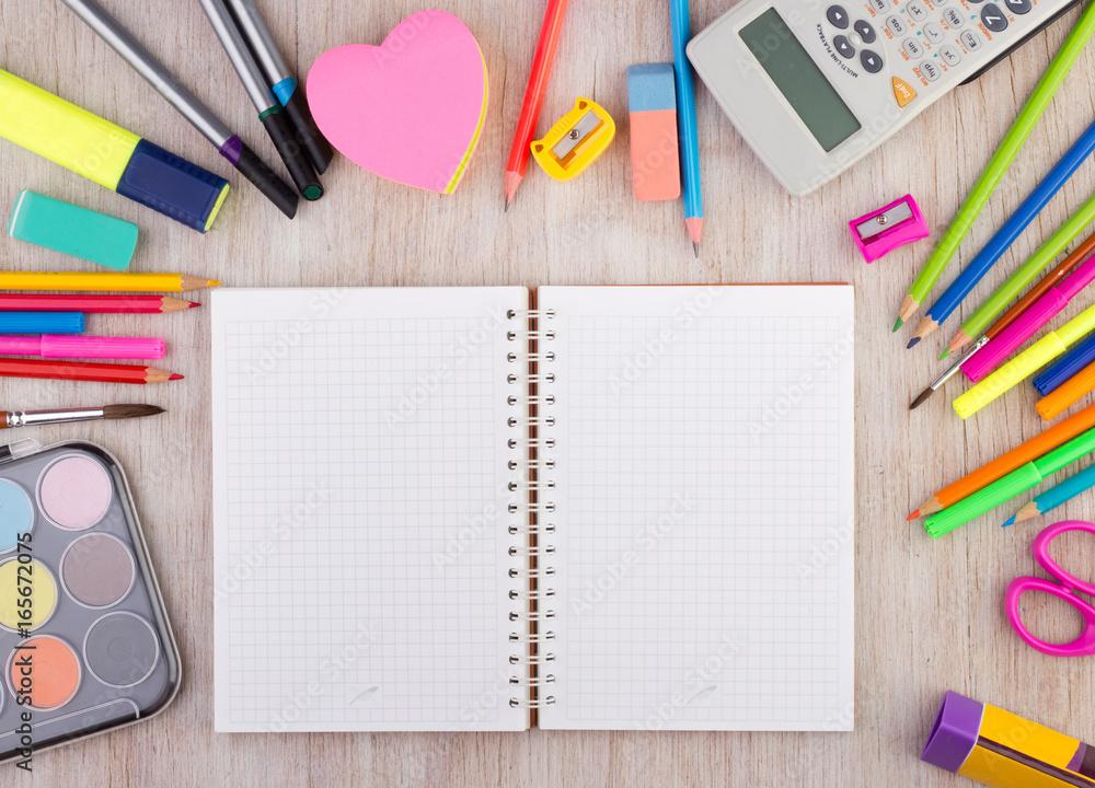 Fototapeta School supplies on wooden desk wirh open notebook